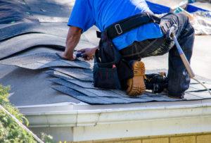 man installing new shingles